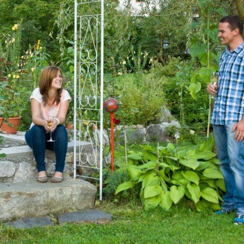 Eine Frau und ein Mann unterhalten sich im hauseigenen Garten
